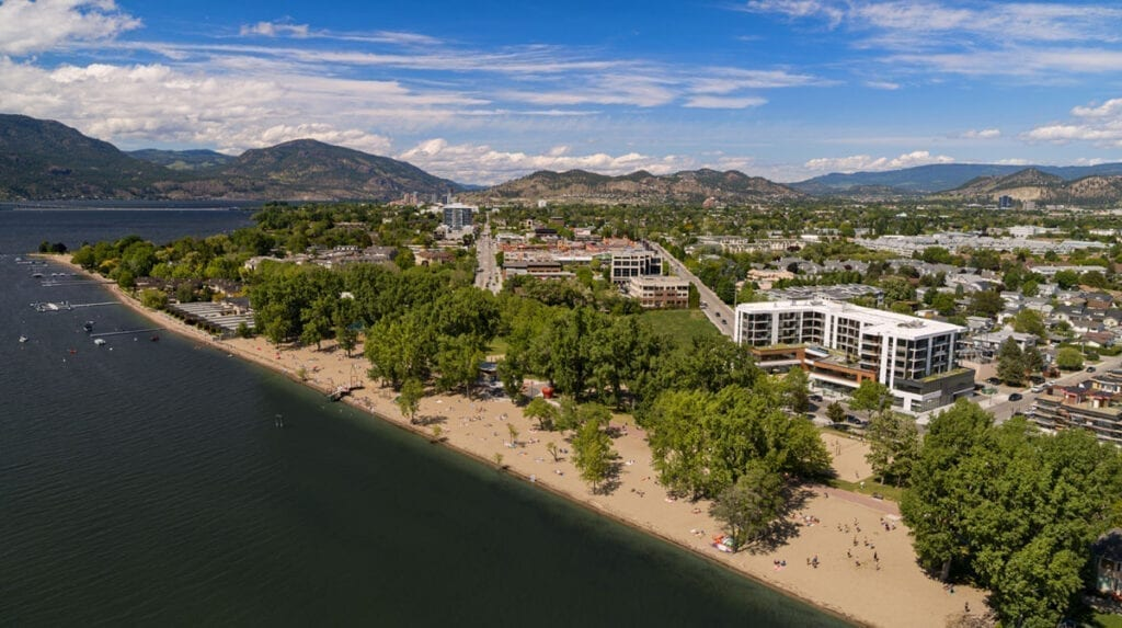 An aerial view of The Shore Kelowna accommodations on Okanagan Lake with Gyro beach in the foreground on a sunny day